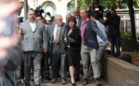 Rolf Harris arrived at court surrounded by bouncers but without his wife