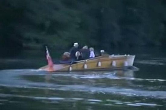 Rolf Harris tried unsuccessfully to evade photographers by leaving his home by boat on Friday morning