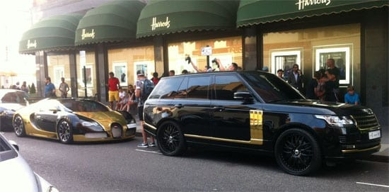 The Veyron travels with a black and gold Range Rover
