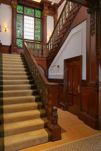 The grand staircase includes a feature stained glass window