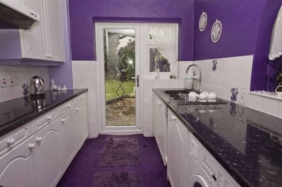 The kitchen doesn't escape the purple touch either with walls and flooring in the owner's favourite colour