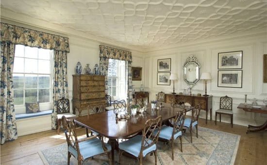 The paneled dining room is completed by a plaster ceiling