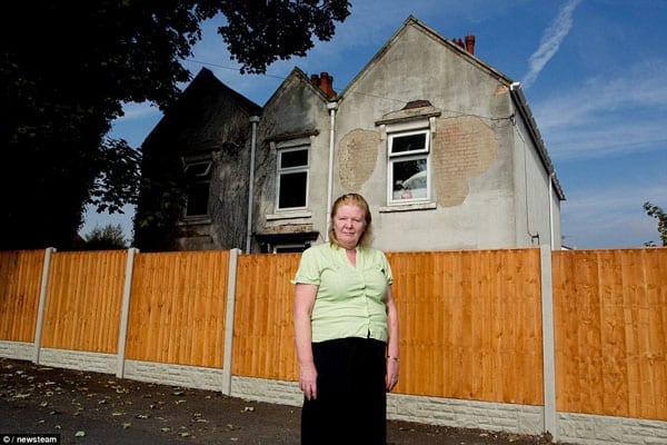 "Wendy Collins stands on land belonging to her neighbours next to the fence that she's termed her personal ""Berlin Wall"""